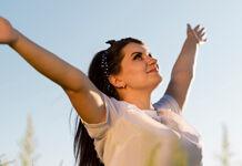 mulher com os braçoes erguidos que tem confiança em Deus
