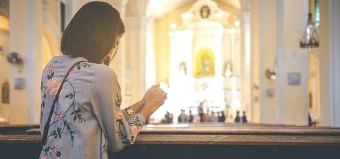 Amar a Deus e ao próximo mulher rezando na igreja